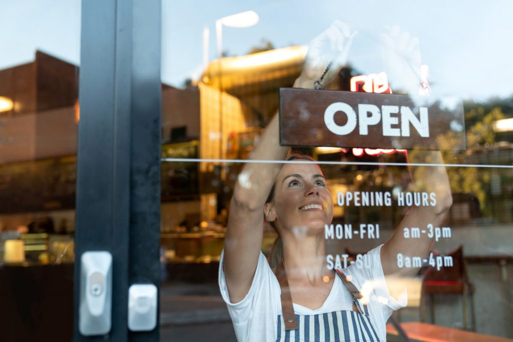 Portrait of a happy business owner hanging an open sign on the door at a cafe and smiling - food and drinks concepts representing Restaurant Brand