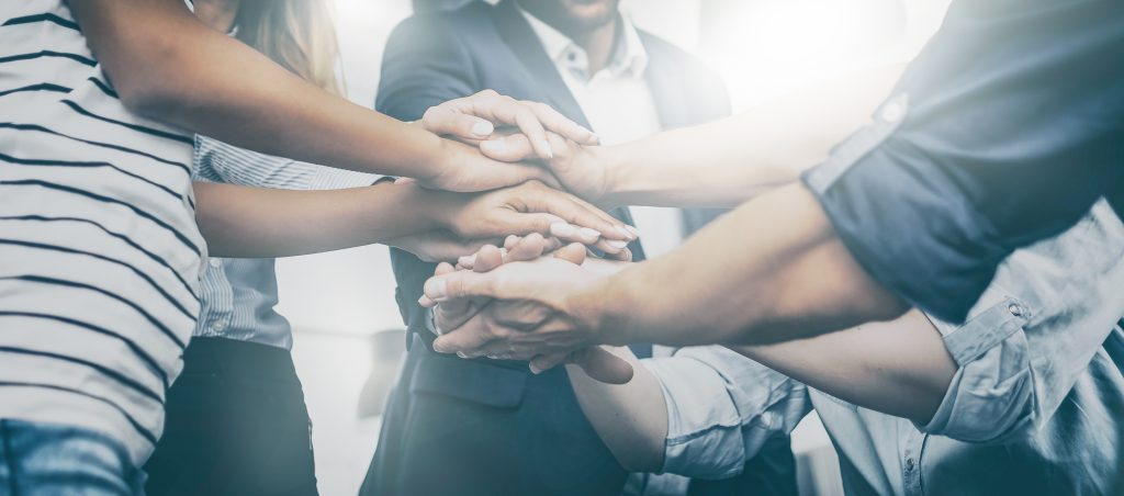 Close up view of young business people putting their hands together like a team. It's a team! Stack of hands. Unity and teamwork concept.