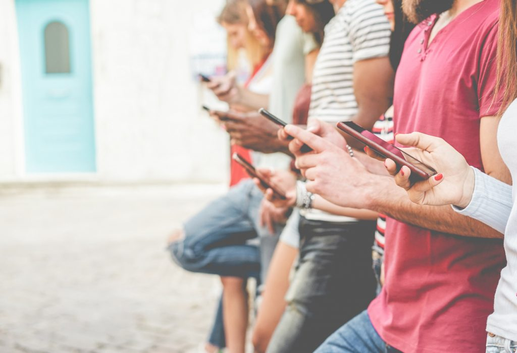Group of friends watching smart mobile phones - Teenagers addiction to new technology trends - Concept of youth, tech, social and friendship - Focus on close-up phone - importance of mobile marketing