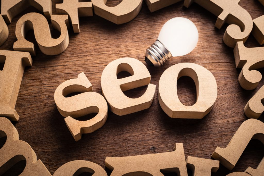 Seo abbreviation in scattered wood letters with glowing white light bulb