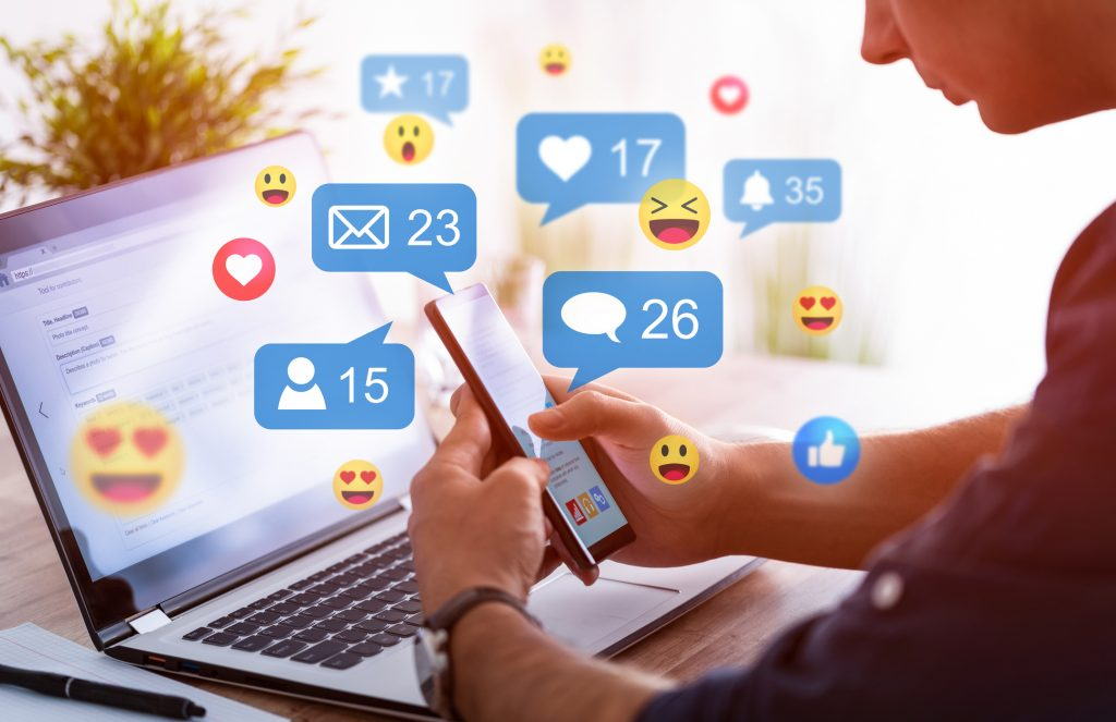 Like and share social media. Hands holding smartphone with social media network icons. Marketing concept. representing social media around the world